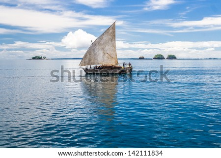 NOSY BE, MADAGASCAR, APR 4, 2008: Unidentified people on a traditional malagasy dhow transporting goods near Nosy Be, Madagascar on apr 4, 2008 - stock photo