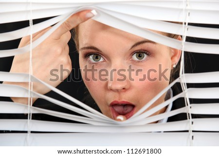 Nosy blond woman peering through blinds - stock photo