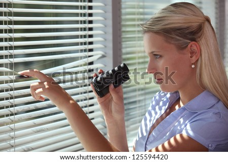 Nosy woman peering through some blinds - stock photo