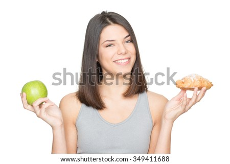 Not a hard choice. Studio shot of an attractive young healthy woman holding an apple and a croissant choosing smiling to the camera - stock photo