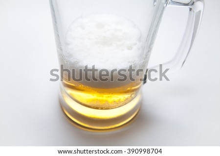 Not completely poured a mug of beer on a white background - stock photo