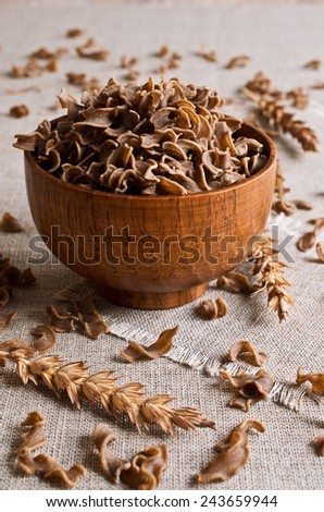 Not cooked pasta brown in a pan on a napkin - stock photo