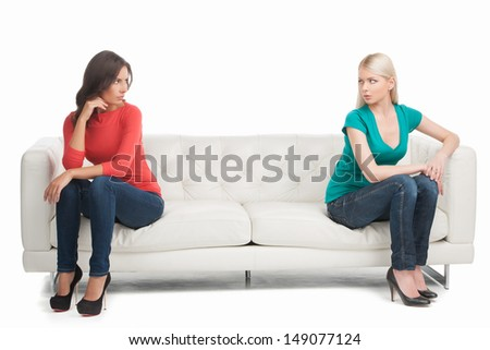 Not friends anymore. Two angry women looking at each other while sitting on the different sides of a couch