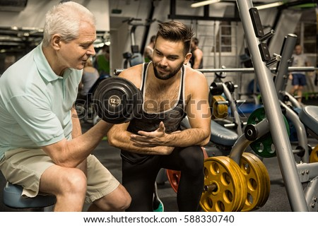 Not giving up. Personal fitness trainer helping his elderly client working out with weights senior man pumping iron at the gym copyspace profession help support sports teamwork activity lifestyle