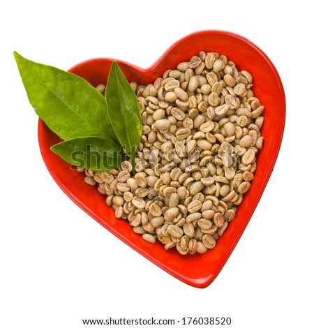 not ground green coffee beans  in a bowl in the shape of a red heart  isolated on white background - stock photo