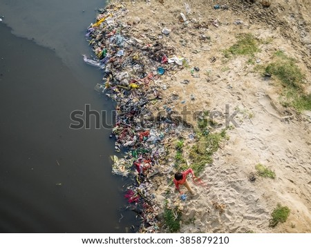 Not recognizable kid playing at the polluted river banks of the yamuna - stock photo