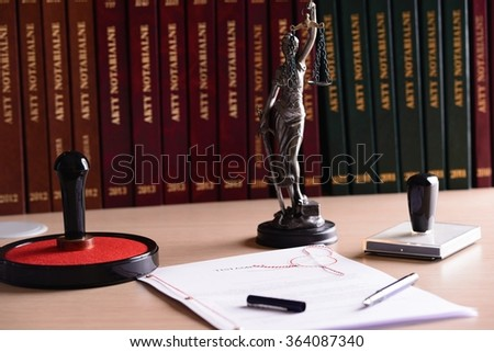 Notary public accessories. Themis with scales of justice and notarial acts in the background. - stock photo