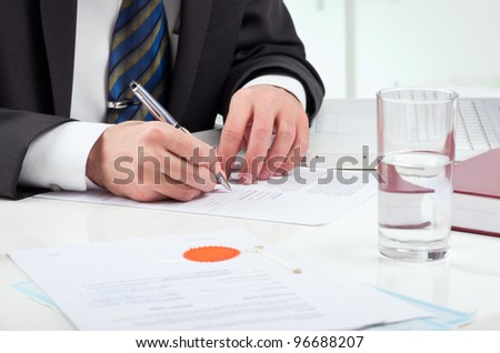 Notary public signing document at his workplace - stock photo