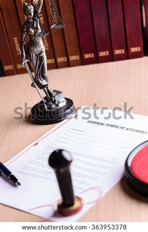 Notary public stamp on signed power of attorney. Pen and Themis with scales of justice in the background. - stock photo