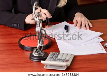 Notary public stamping the agreement on rosette in notary office - stock photo