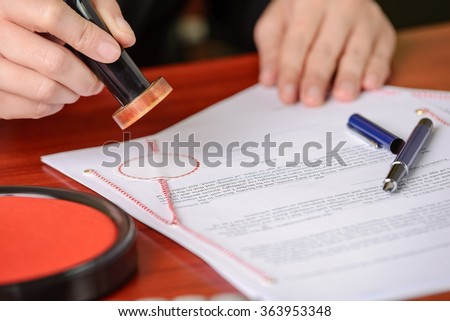 Notary stamps signed contract in his notary's office - stock photo