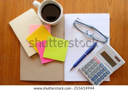 note book and calculator on wooden table with coffee  - stock photo