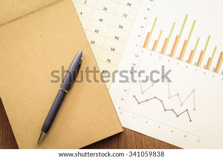 note book and chart on the wooden table with vintage color style