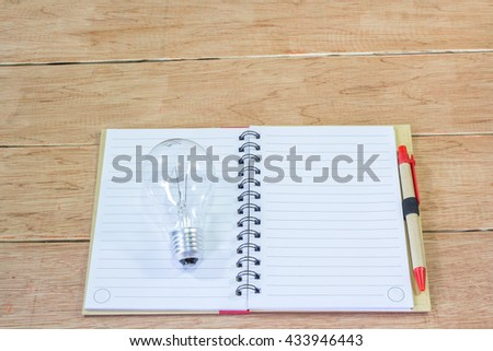 Note book and lamp on wooden background