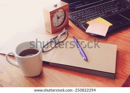 note book and laptop on wooden table with retro filter effect