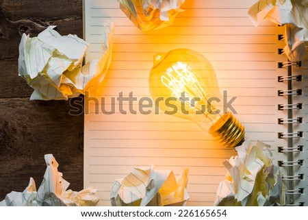Note book and light bulb on wood table - stock photo