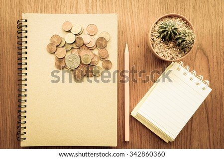 note book and money  on the wooden table with vintage color style - stock photo