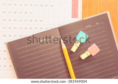 note book and planner on the wooden table with vintage color concept - stock photo