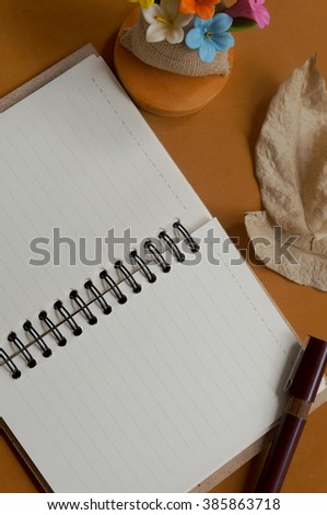 Note Book, Artificial flowers, Dry leaf on the leather brown color wallpaper