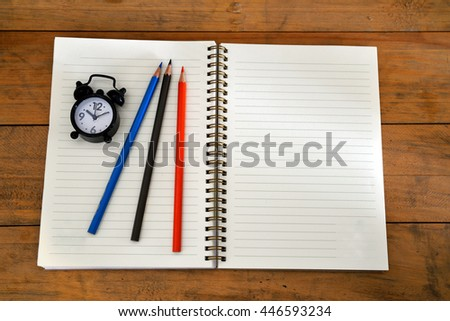 Note book , color pencil and clock on wooden background