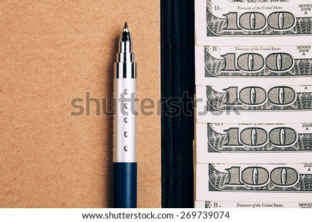 note book, pen and dollars, planning and saving  money concept, closeup - stock photo