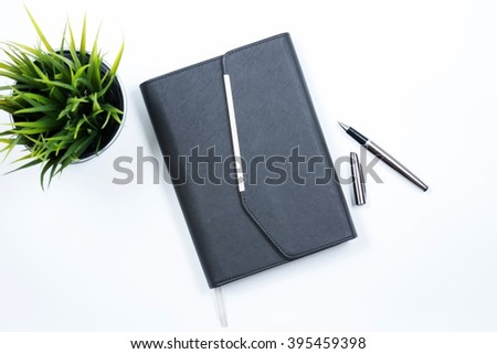 Note Book with black pen and grass in the bucket arrange in flatlay with white background. Selective focus with shallow depth of field. - stock photo