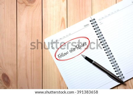 Note Book with Black Pen. Writing FOLLOW THE RULES in Red Circle with wooden pallet background.
