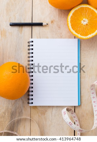 note book with orange on wooden floor,top view - stock photo