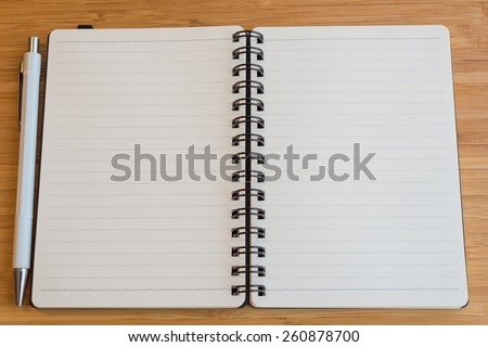 Note book with pencil on a wooden desk.