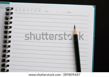 Note book with Pencil  on black background