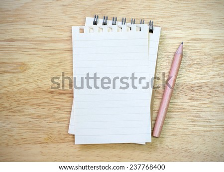 note book with pencil on wood table