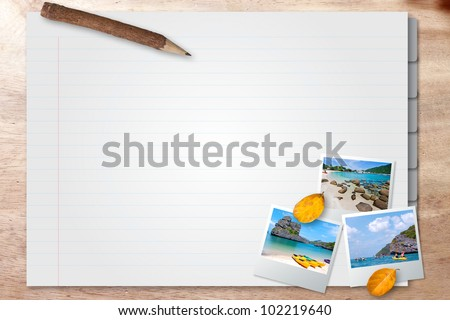 Note book with photo frame on wood background - stock photo