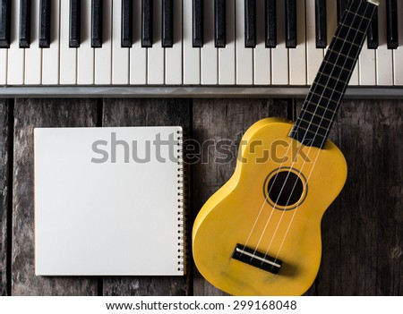 note book with piano key and ukulele on a wooden floor.
