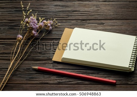 note book with red pencil and flower statice on wooden background, copy space