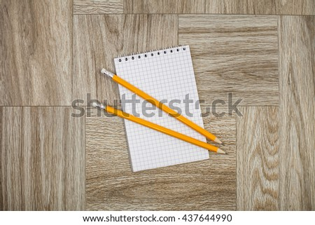 Note book with yellow pencil on a wooden texture - stock photo