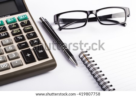 Note pad, pen, glasses and pocket calculator on a white background - stock photo
