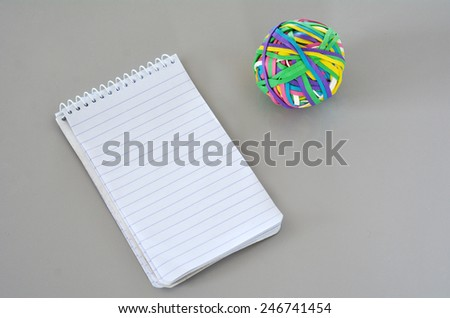 Note Pad with Rubber Band Ball on on office desk. concept photo copyspace - stock photo