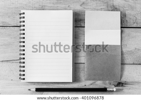 note paper and note book on wooden background ,monochrome filter - stock photo