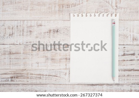 Note paper and pencil on wood table - stock photo