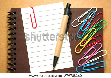 Note paper clip on notebook with pen and colorful paperclips on brown cardboard background - stock photo
