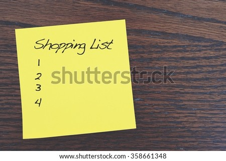 note paper on vintage wood wall with word shopping list - stock photo