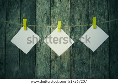 note paper with cloth clip hanging on rope over wooden background