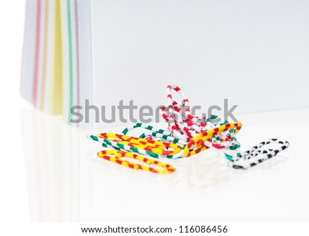 Note paper with colorful paper clips on white background