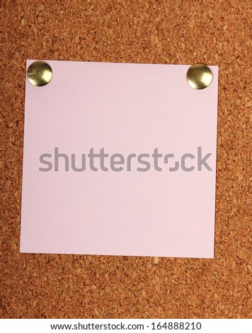Note paper with pin on cork board - stock photo