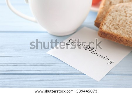 Note paper with text GOOD MORNING on wooden table