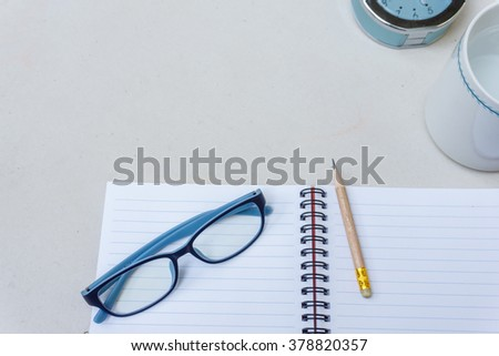note,pencil, glasses,clock and cup on white table