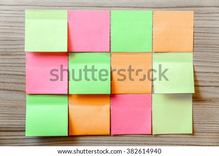 Note stickers in a grid on wood background