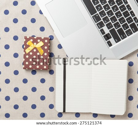 Note with gift and laptop on polka dot background.