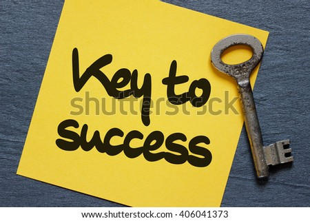 Note with key to success concept. Dark stone background