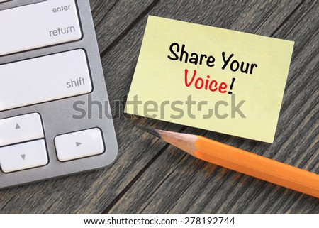 note with the message of share your voice, with desk background - stock photo